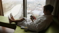 Young man texting on smartphone sitting on a bed at apartment near window with great city view 45923010