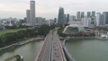 Aerial for Singapore with many cars on the bridge above the lake and city buildings background. Shot 45946641