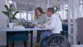 successful disabled, creative freelance businessman in wheelchair With woman discuss startup 46011621