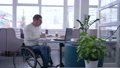 developing of Disabled mature man in wheelchair into glasses works on laptop during distance online 46011667