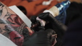 Macro view of professional tattoo master is painting with red ink, making cover. Works in black 46334955