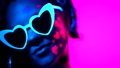 Portrait of fashion model woman with heart shaped glasses in neon light. Fluorescent unusual makeup 46375252