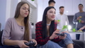 female teenager winning videogame competition with girlfriend sitting on sofa on backgrounf of 46452767
