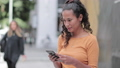 Portrait of hispanic young adult female using smartphone on busy city street 46486339