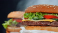 Fresh yummy grilled burgers rotating on black smoke background. Meat patty, tomatoes, cucumber 46500962