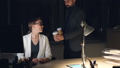 Caring male colleague bearded man is bringing take away coffee to tired young woman working on 46584975