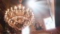 Orthodox, Christianity, church. Beam of light shines over old gondel chandelier with candles hanging 46780840