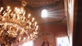 Orthodox, Christianity, church. Beam of light shines over old gondel chandelier with candles hanging 46780860