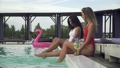 Young girls have fun in the outdoor swimming pool creating huge water splashes by slim slender legs 46809710