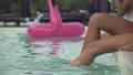 Slender slim female slender legs create huge water splashes in the outdoor swimming pool. Leisure 46809712