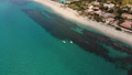 Two pedal boats float on clear turquoise sea waters by sandy beach of Italian resort. Aerial shot 46891078