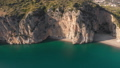 Flying away from steep rocks above turquoise waters of a sea. Aerial shot of Italian coastlaine in 46891088