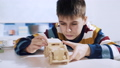 A boy constructs a car from a wooden 3d puzzle. 47091757