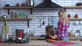 Cute mother in plaid shirt with long blond hair cooking breakfast and small naughty girl bite one 47158270