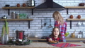 Young mother in plaid shirt with long blond hair cooking breakfast and small naughty girl bite one 47158272