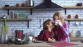 Mom and little daughter in plaid shirts have breakfast in the kitchen eating cookies and a drinking 47158273