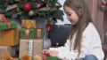 Little cute girl with long brown hair sitting near christmas tree and open presents 47158709