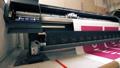 Industrial printer making big colorful banner in workshop  47172130