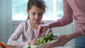 Little girl eating broccoli and spinach. 47225598