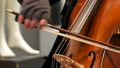Street musician playing the cello close up view. Cellist in gloves gently bows strings 47302427