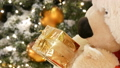 White teddy bear, holds a box with a gift in his paws and moves on the background of the Christmas 47302429