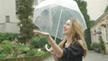 Charming blonde woman enjoys summer rain walking with umbrella 47596468