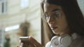 Young girl in glasses reads something in her smartphone 47596477