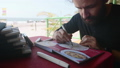 Man sits in cafe and drawing image of Indian food in sketchbook by art markers 47624751