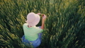A female farmer is photographing ears of green wheat using a smartphone. 47681714