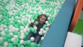 Little girl playing with small balls on playground in children's center 47695417