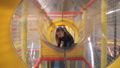 Little girl crawling through tunnel on children's play ground indoors 47695448