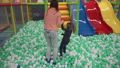 Mother and daughter walking on balls on playground in children's center 47695459