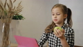 Little girl eating apple and using tablet computer in the kitchen. 47705939