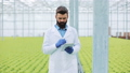 Agricultural engineer analysing plants in greenhouse. Agronomist in greenhouse wearing white coat 47737507
