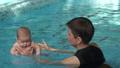 Woman teaching baby to swim 47793123