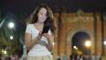 Tourist girl using mobile phone standing against Arc de Triomf, Barcelona 47846116