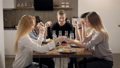 Great company of close friends sitting at dinner table holding hands giving prayer before dinner. 47864568