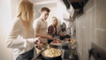 Side view of friends cooking all together in kitchen, tasty food for the evening. 47864572
