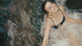 Summer vocation, mountain. Charming young brunette woman fixes her hair standing in the cold water 47921269