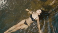 Summer vocation, mountain. Charming woman enjoys water in cold mountain river lying on the rocks 47921277