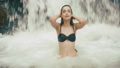 Summer vocation, mountain. Charming young brunette woman splashes water standing in the waterfall 47921281