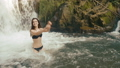 Summer vocation, mountain. Charming young brunette woman splashes water standing in the waterfall 47921283