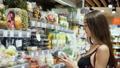 Adult young beautiful woman model in food store chooses fresh berries diet FullHD. 47942688