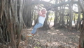 Little cute child girl is swinging on liana under banyan tree in slow motion 48006808