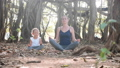 Little child girl with young mother meditating together under banyan tree 48006821