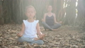 Little child girl with young mother meditating together under banyan tree 48006824