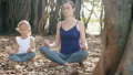 Little child girl with young mother meditating together under banyan tree 48006828