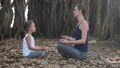 Little child girl with young mother meditating together under banyan tree 48006850