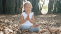 Little child girl meditating alone under banyan tree  48006862
