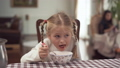 Cute blond girl with pigtails eating borshch sitting at the table in modern kitchen on blurred 48030412